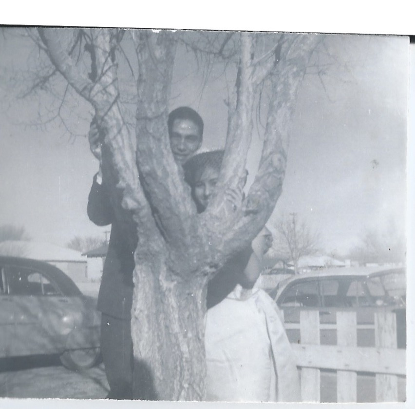 Norma with unknown man posing by tree